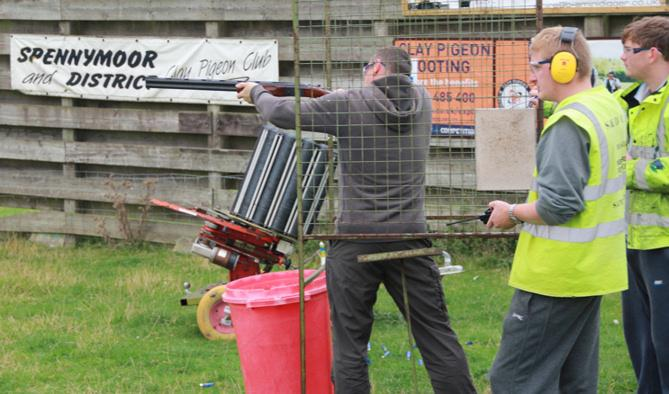 Annual Clay Pigeon Shoot - Peter Kerr gets some expert tuition at the Novice stand ...