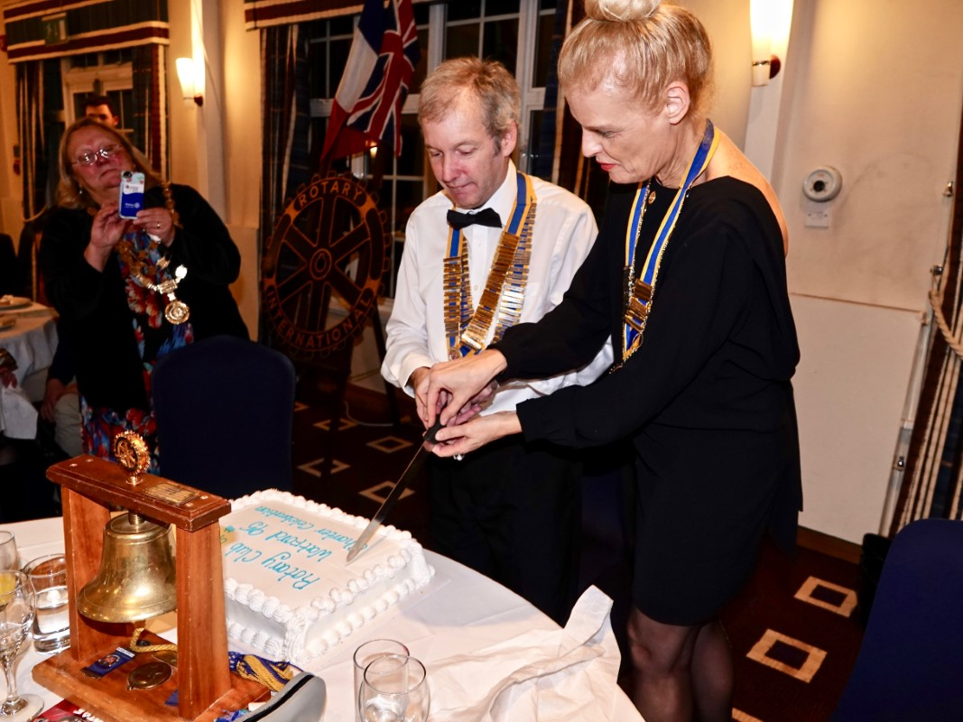 Watford Rotary Club Celebrates 95 Years Of Service - Club President Tim Cox cutting the cake with Isabelle Baumann, Nancy's President