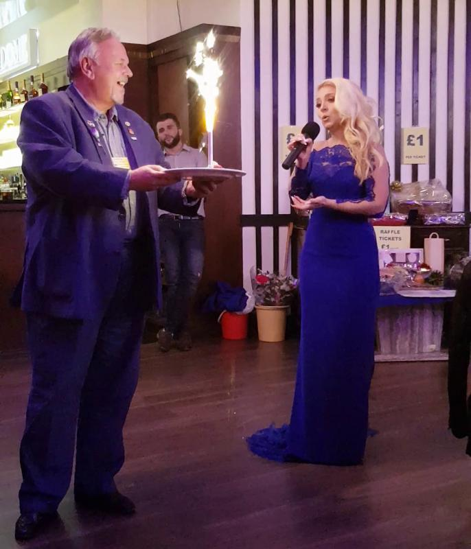 District Governor's Newsletter - April 2019 - DG Dave being serenaded on his big birthday by Emily Haig at the Jaipur Limb Dinner