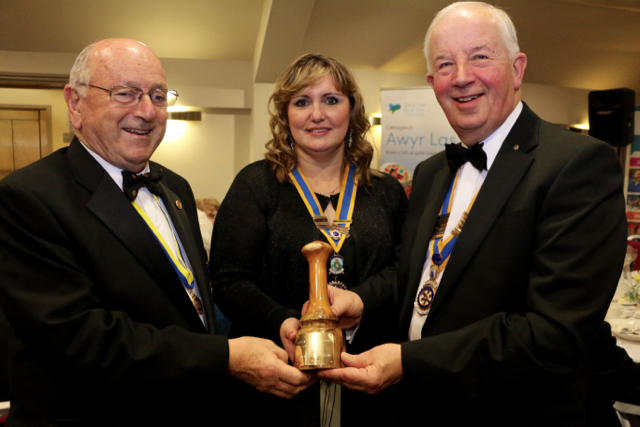 Holyhead Rotary Club 70th Charter Dinner - President Robyn Williams being presented with a gift from President Jackie Blackwell, Llangefni Rotary Club and PHF and past president of Llangefni Rotary Club Rotarian Mike Wilson 0009 (1)