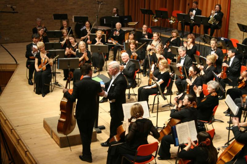 Feb 2012 Charity Concert  West Road Concert Hall Cambridge  - Guy Johnston who played the cello solo parts in the Tchaikovsky Rococo Variations with conductor Leon Lovett watched by part of the orchestra.