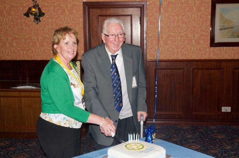 Cowdenbeath Rotary Club celebrates its 90th birthday. - Lesley helps Past President and longest serving Member Arthur Nevay cuts the cake.