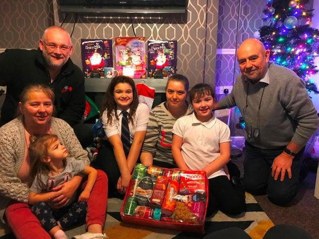 Christmas Hamper Appeal 2020 - One of the families who received hampers in 2019 with Kevin Dobson from CAP (l) and Bob Guard from the Rotary Club of Wakefield Chantry (r).