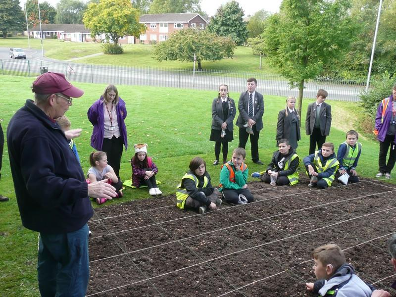 Planting Crocus bulbs at the Town Hall - Rtn Ken Tonge informing the children the significance behind the planting of Purple Crocus