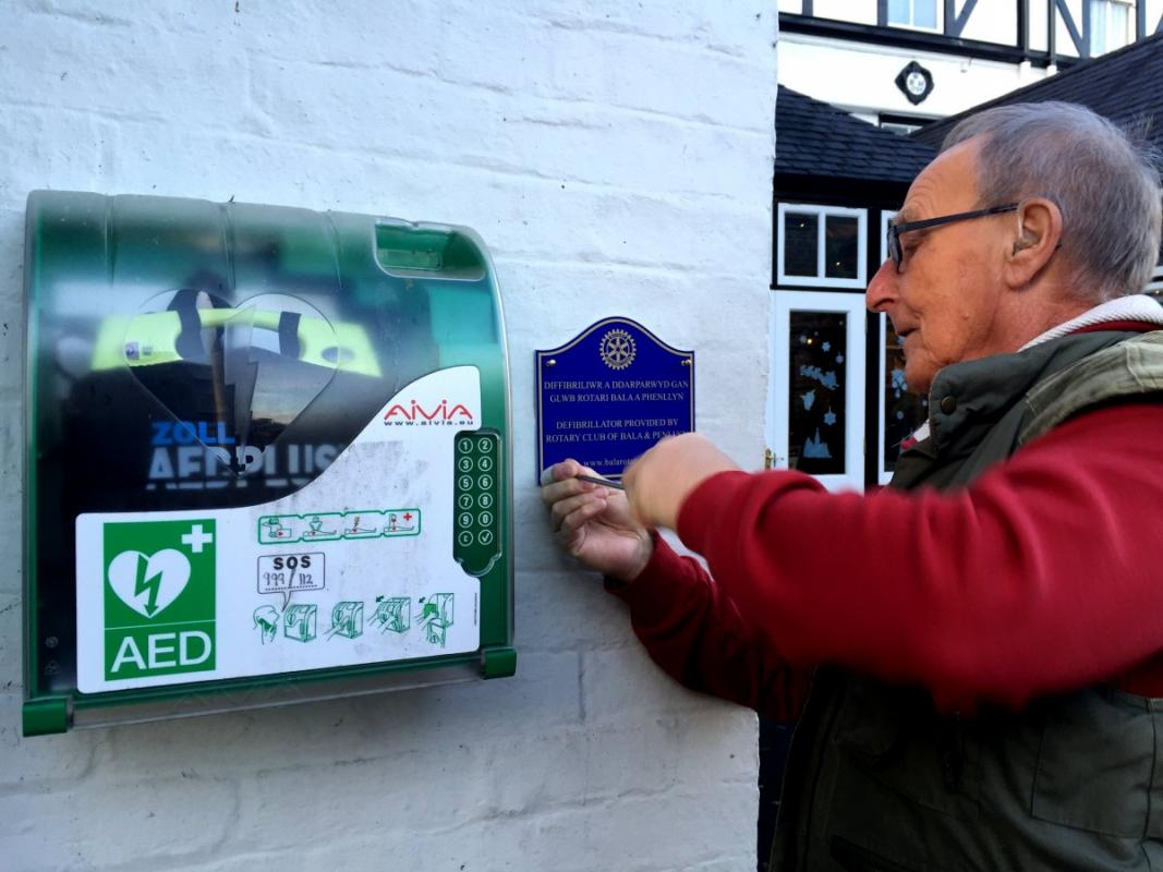 Bala Rotary Club provides a defibrillator for the High Street - Dr. Gareh shown installing the plaque to say the defibrillator was provided by our Rotary Club.