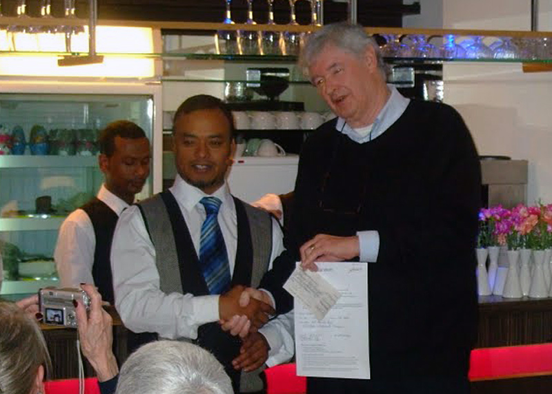 Charity Curry Night - Clyde receives a cheque for 680 pounds.