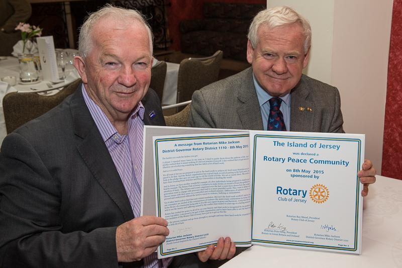 Jersey a Rotary Peace Community - Rotary International in Great Britain and Ireland President, Peter King and District Governor 1110 Mike Jackson display The Rotary Book of Peace after adding their signatures.