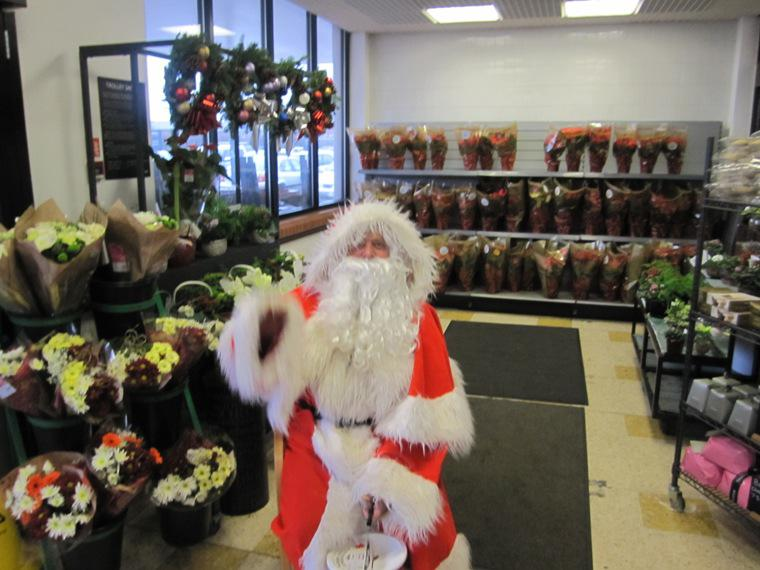 SANTA AND THE MUSICAL SANTA SLEIGH VISITS THE MARTON BOOTHS STORE  - Santa looks well sitting with a floral background.