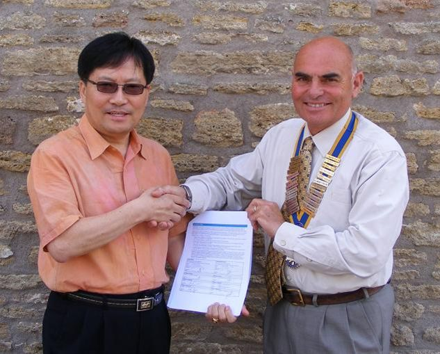 Rotary Links across the world with Matching Grant - Presidet Mike Cole and Rotarian Chul Hee Park with the signed matching Grant Document