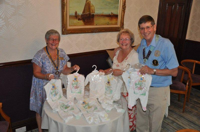 District Governor's Visit - President Hazel presents D.G. Roger and his wife Mary with babygrows to help fill an Aquabox.