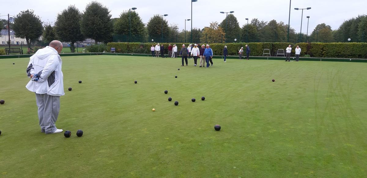 Newbury Bowling Club - Cliff Oxlade observes which woods are nearest the jack. John Green and Alan Cadden roll from the far end.