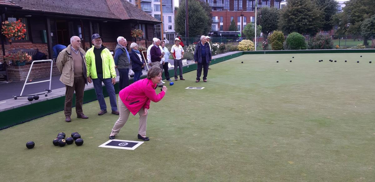 Newbury Bowling Club - Lorna performs a stylish roll, but shouldn't she be standing on the mat. Nick and Graeme turn a blind eye.