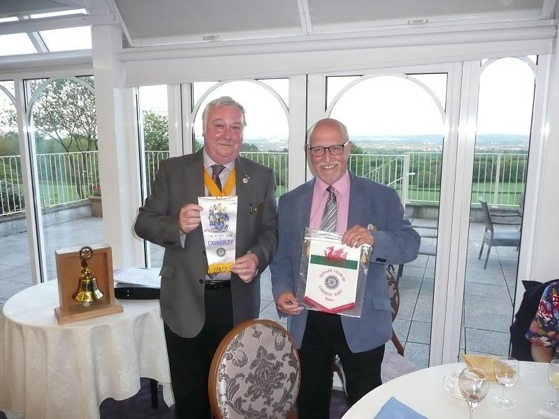 Interaction/co-operation With Other Clubs, District and RIBI - Here President Elect Paul Gregory exchanges banners with President Alan Costello of the Rotary Club of Camberley on a visit to Cardiff of club members and partners totalling 23. An excellent evening of fellowship was enjoyed by all.