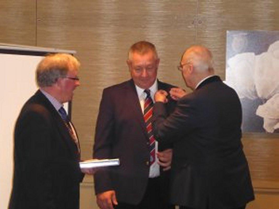 Induction of New Members - Alan pins on Mark's Rotary Badge