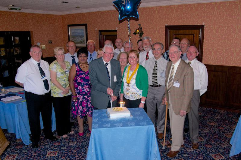 Cowdenbeath Rotary Club celebrates its 90th birthday. - Members gather round while Arthur Nevay cuts the cake.