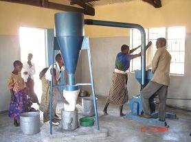 Our Malawi Grain Mill and Store - Committee member operating the mill as a female customer takes care of her maize flour