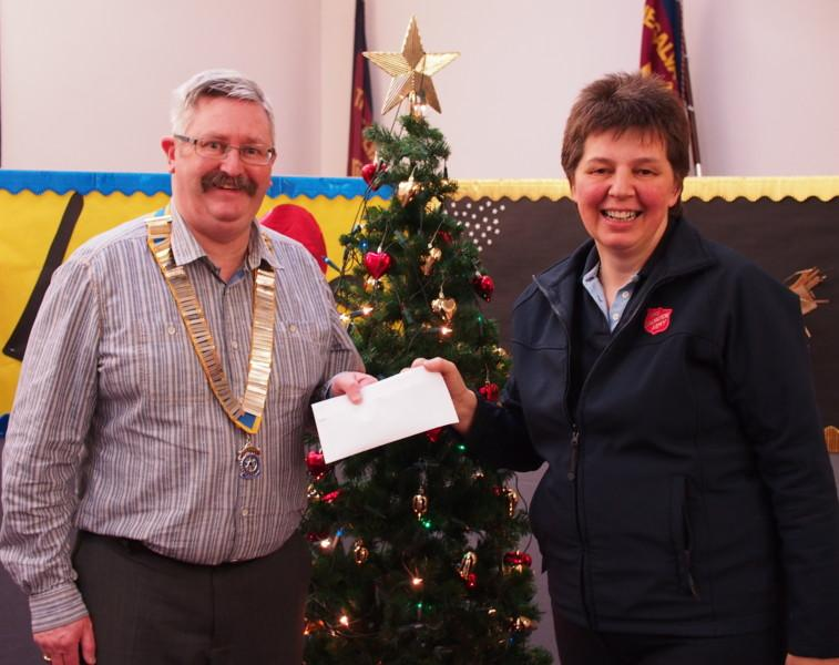 Cheque presentations - Major Helen Young, Commanding Officer, Army Arbroath, receives £270 from President David Miller.The money was raised by the Club's Dickensian Carollers just before Christmas 2015