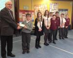 Support for local school library - Head Teacher Debbie Broadley and the pupils welcome Ewan's big cheque