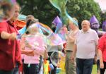 About Our Club - Summer Fair attendees, seen through a cloud of bubbles!